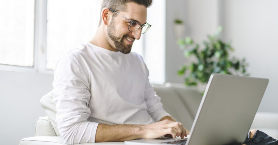 Young attractive guy is browsing at his laptop, sitting at home on the cozy beige sofa at home, wearing casual outfit